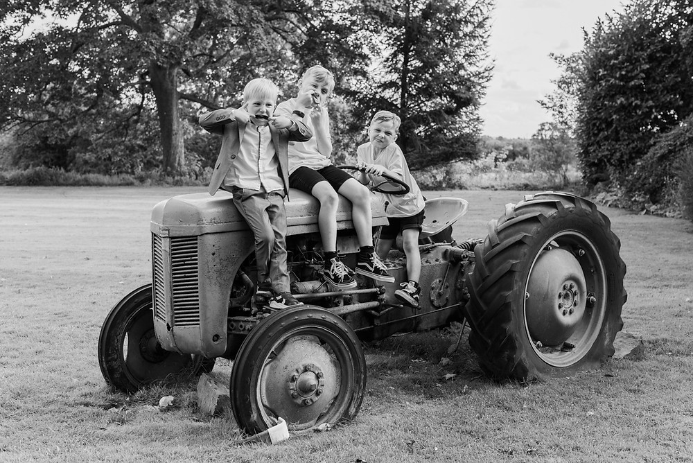 Fun Wedding photographer Leicestershire. Kids at a wedding at Ashton Lodge on a vintage tractor pulling funny faces.