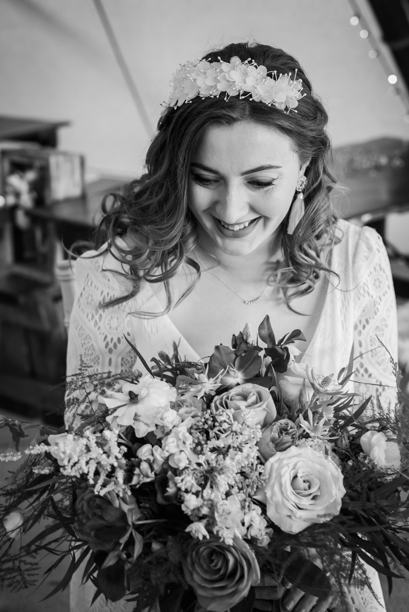 Bride in white dress and floral head band with bridal bouquet of flowers. Black and white wedding photography Leicester