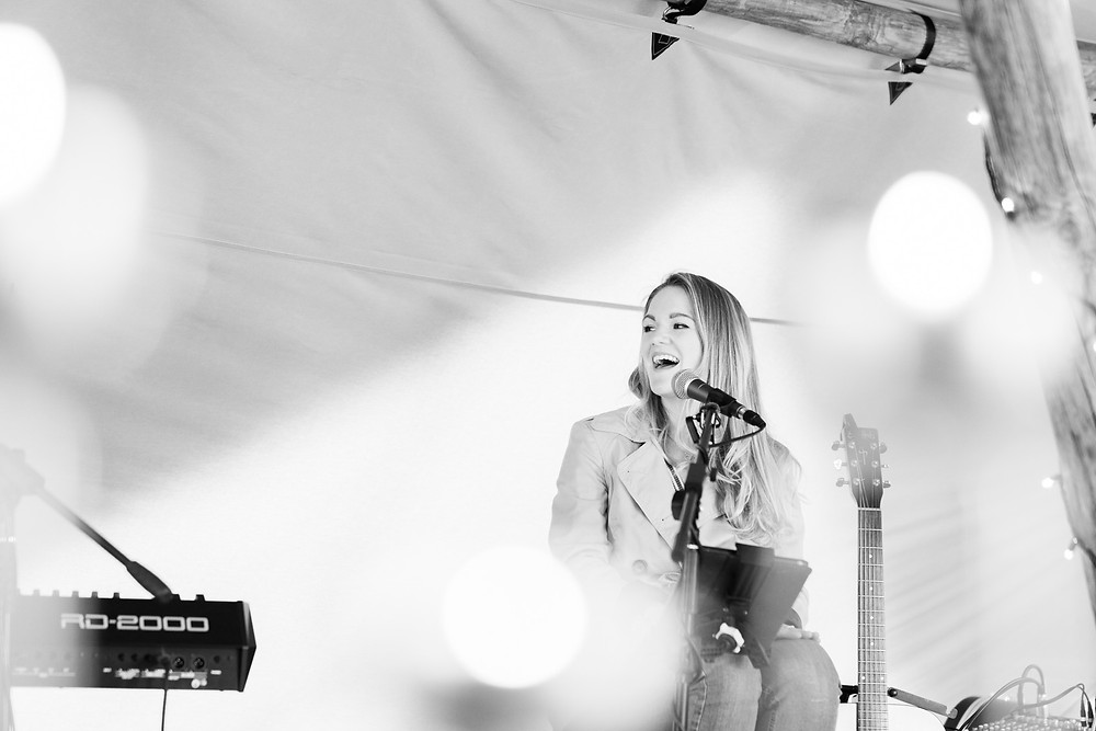 Black and white image of Heather Flint Music singing in a tipi wedding venue.