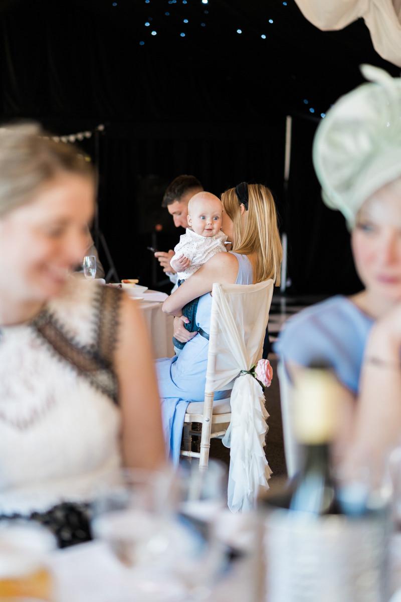 Baby wedding guest having fun. Wedding photograph from across the wedding reception at Ashton Lodge.