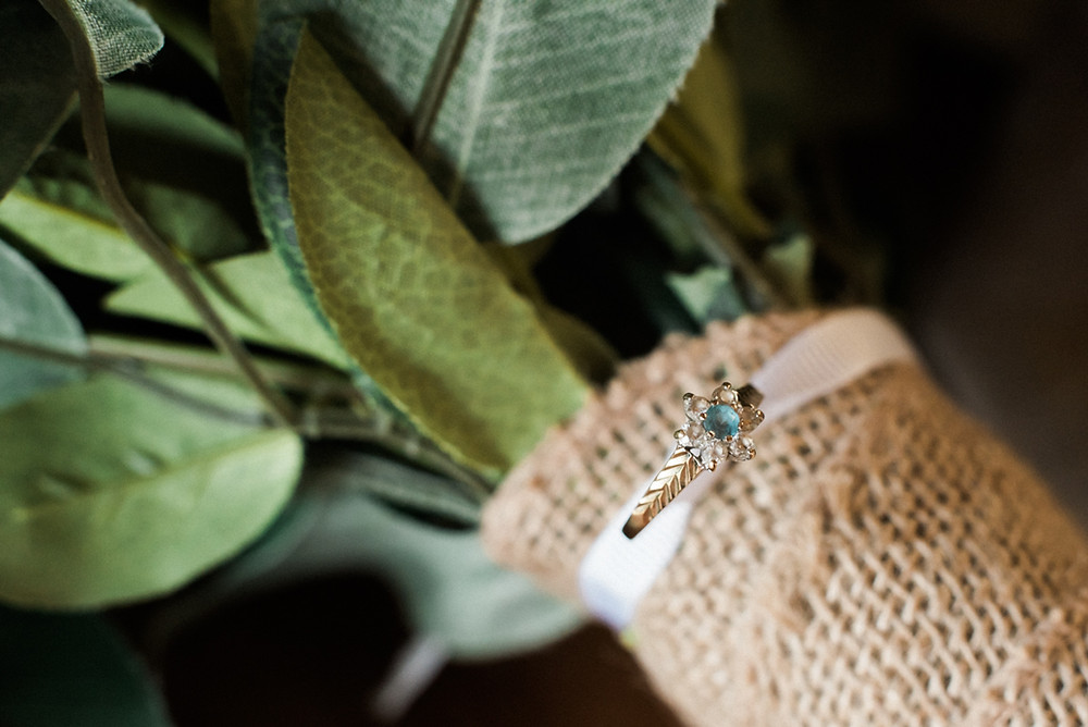 Artificial wedding bouquet with macro focus on a gold and sapphire engagement ring. Hessian boho bridal bouquet. Eco friendly wedding flowers. Wedding photography Leicestershire.