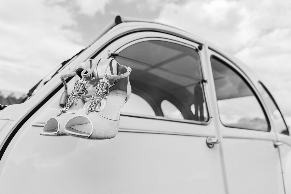 Wedding shoes on the wing mirror of a Citroen 2CV at The Hill Farm House. Wedding photography Leicestershire