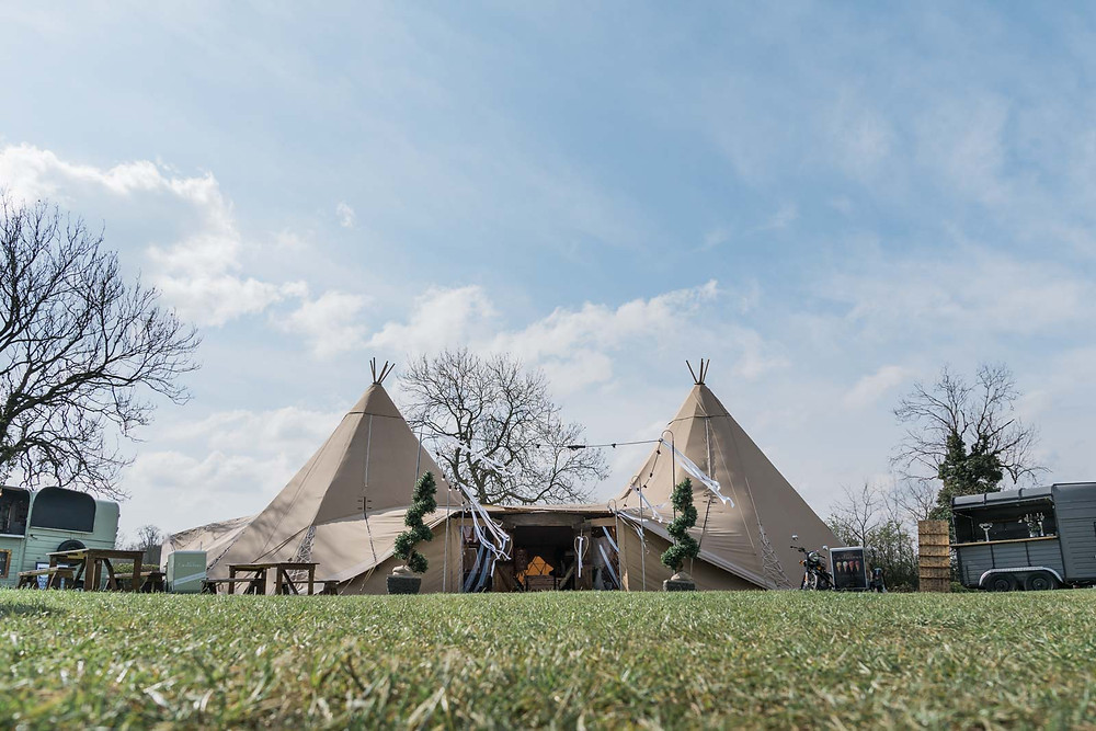 Two hat tipi tipee wedding venue with outdoor horse trailer bars and dressed as a rustic wedding venue