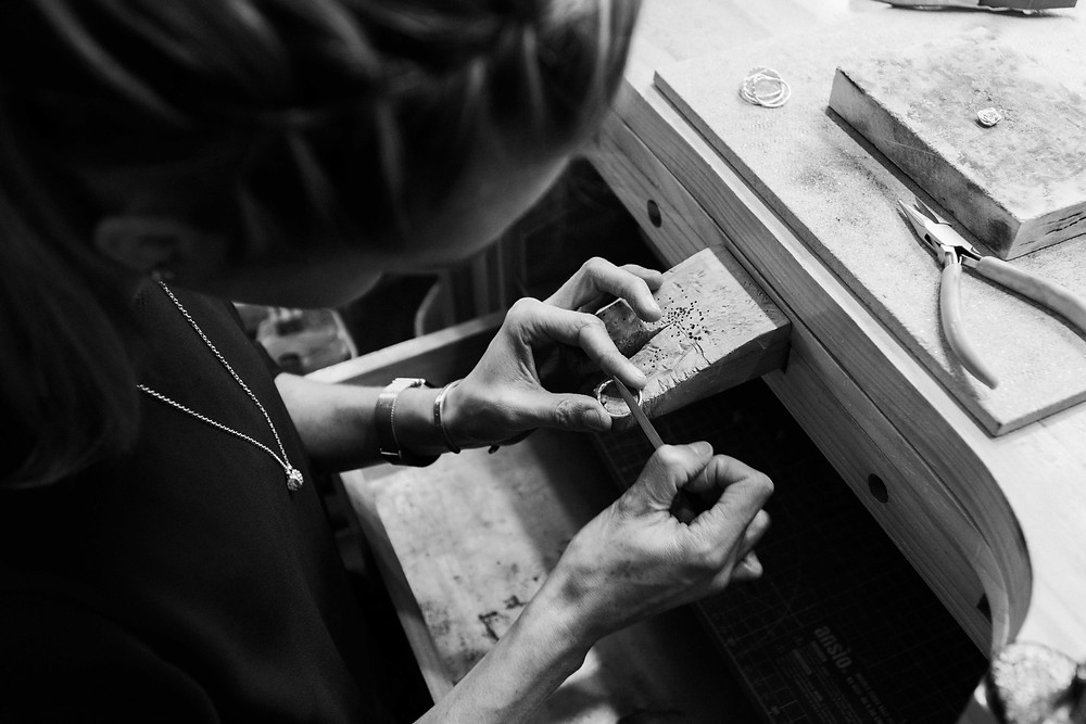 Lucy Flint working on a ring at her workbench in her Oakham boutique. Lucy Flints' silver bracelets could make an ideal choice for your bridesmaids. Image by Darley and Underwood Photography. Film wedding photography.