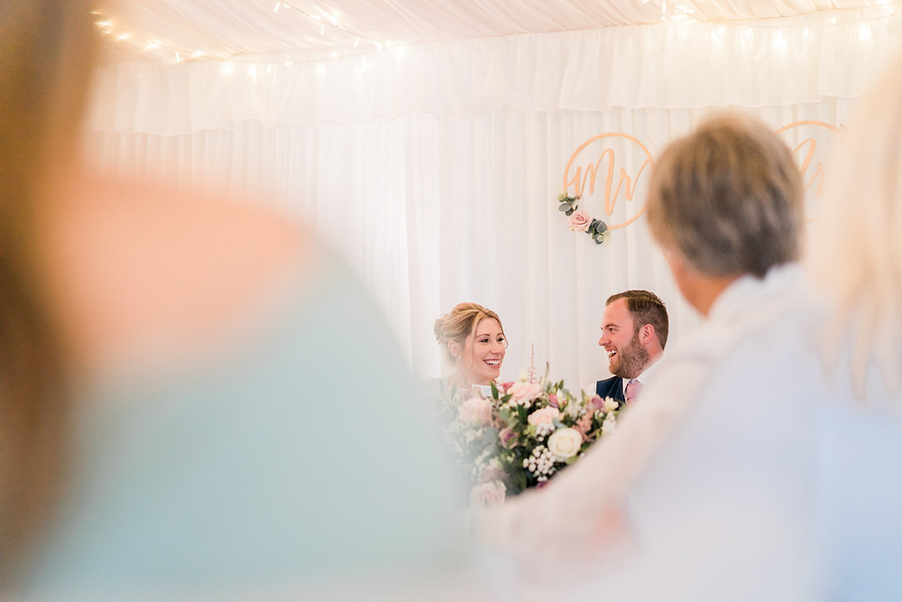 A very happy bride and groom at the top table framed by wedding guests. Warwickshire wedding at Aston Lodge Country House.