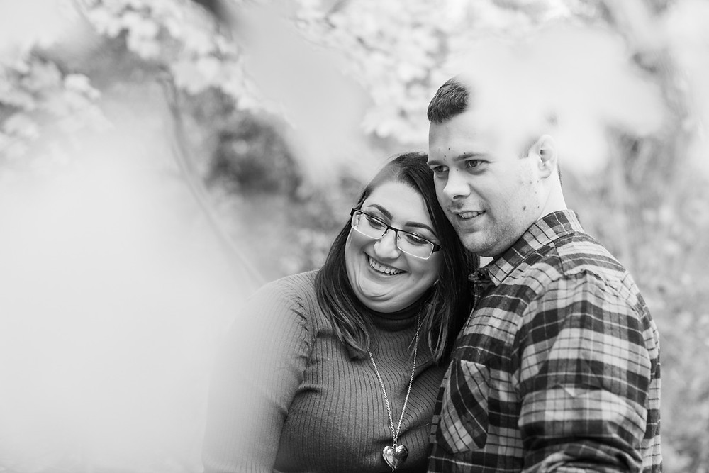 Couple enjoying an autumnal walk at Kingsbury Water Park, Warwickshire. Smiling arm in arm and photographed through autumnal leaves. Black and white engagement photography