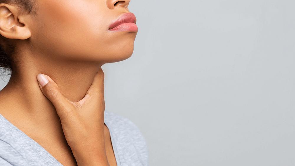 Mulher com mão na garganta preocupada com tireoide