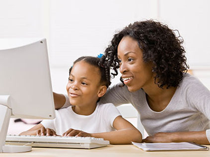 mom-and-daughter-looking-at-computer-mon