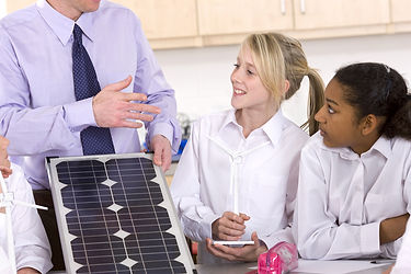 students and teacher with a solar panel
