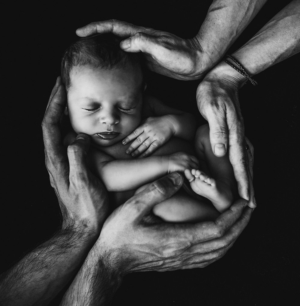 Bebé arropado por las manos de mamá y papá