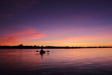 single person in kayak on indian river lagoon during sunset