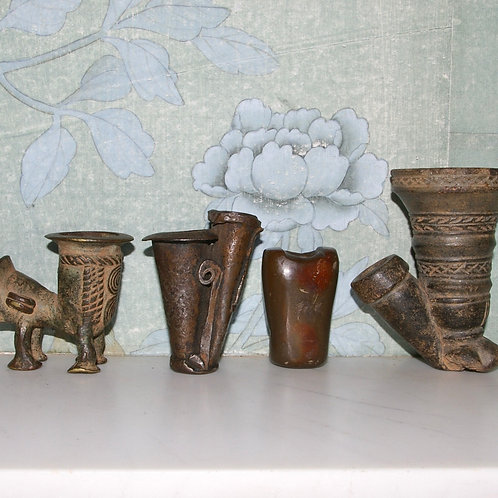Three Cameroon pipe bowls and a Native American pipe bowl.