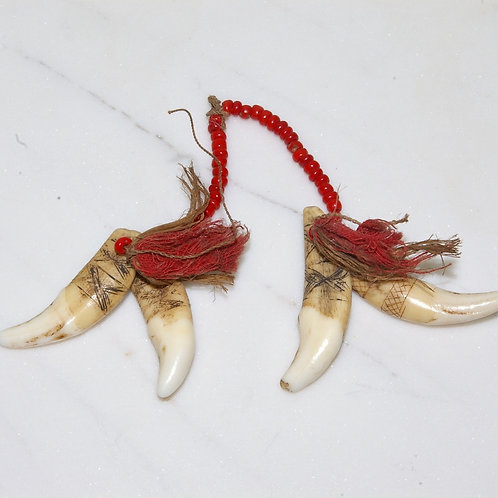 Four Admiralty islands carved dog teeth with beaded cord. Possibly an ear drop.