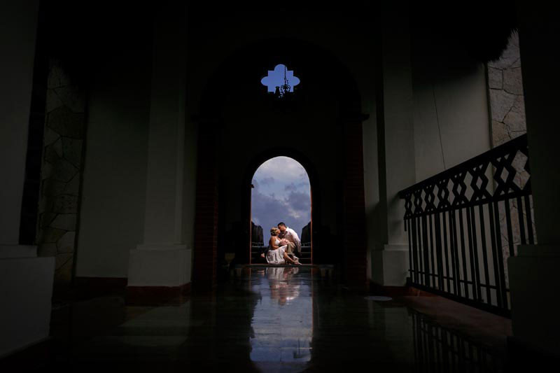 Bride and groom through dark archway