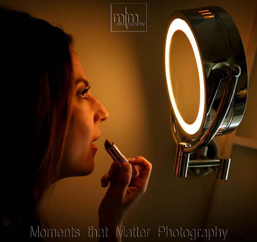 Bride applying last touch of lip stick