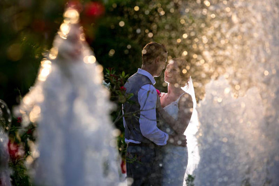 Bride and groom throught water fountain