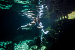 Cuple underwater Trash the Dress session in a Cenote