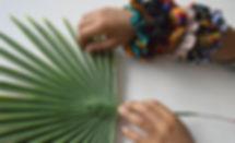 mains d'enfant présentant des chouchous pour cheveux au poignet avec une feuille de palmier pour l'été