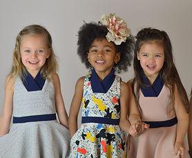 trois petites filles souriantes qui portent des robes de la marque Koh mabby, se tenant la main