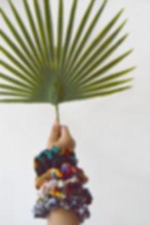 bras d'enfant avec le poignet rempli de chouchou pour les cheveux en wax, coton, lin tenant une feuille de Palmier