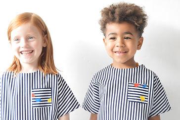 une petite fille et un petit garçon portent le même vêtement en côton rayé pour l'été et sourient. Ce sont des blouses, top Picasso
