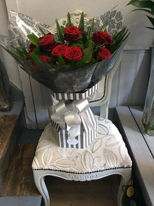 One dozen red roses in an aqua pack