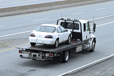 Car loaded on flatbed carrier tow truck