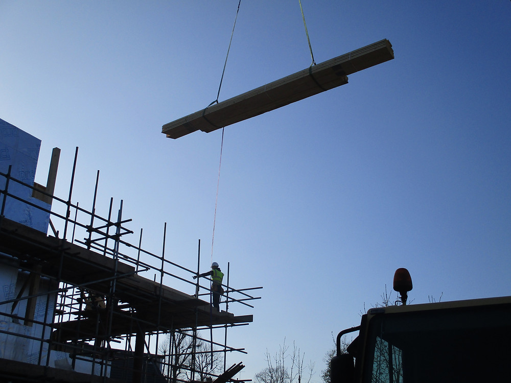 Crane lifting timber on to construction site