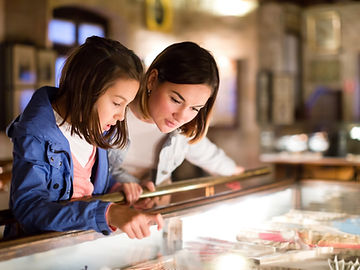 mother and daughter exploring exhibitions of previous centuries in museum