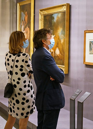Couple looking at paintings in a museum