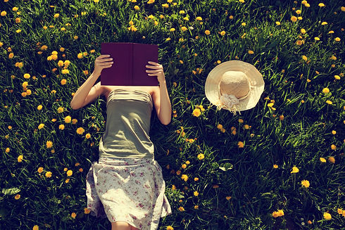 Girl lying in grass, reading a book. Int