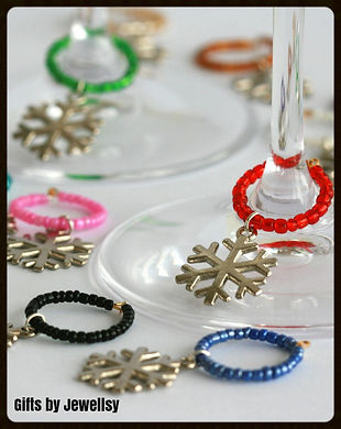 Multi-coloured shiny, beaded wine glass charms with snowflake charms placed delicately around two wine glass stems to decorate a table place setting.