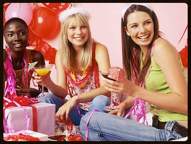 Three young, smiling women enjoying a cocktail at a bachelorette hen party wearing tiaras and streamer string necklaces.