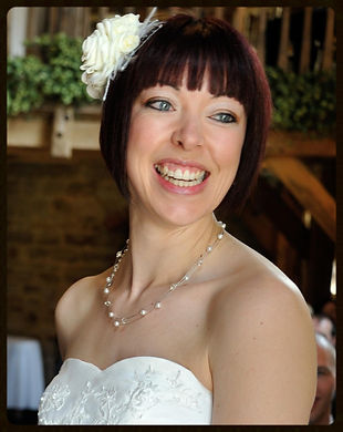 Mel from Jewellsy smiling while standing radiant at the front of family and friends on her wedding day wearing a beautiful white, heart neckline wedding dress; a gorgeous white fascinator and a stunning multi-strand Swarovski crystal beaded necklace.