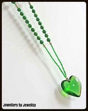 Glistening large glass green heart pendant hanging from a necklace chain made from green pearlescent beads and green seed beads.