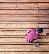 A worker painting exterior wooden pool d