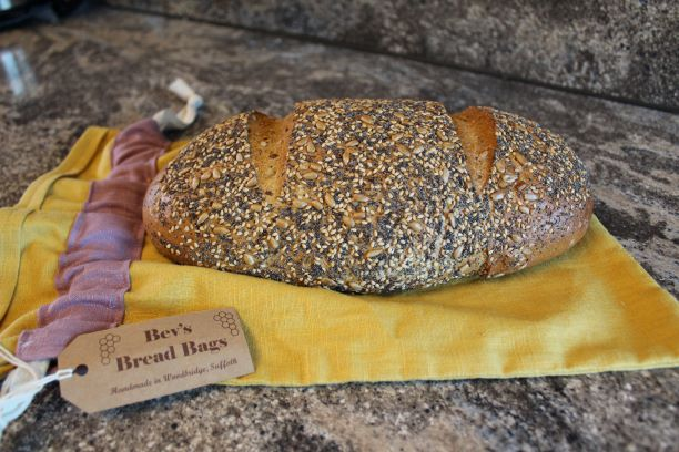 A sour dough loaf on an ochre linen brea