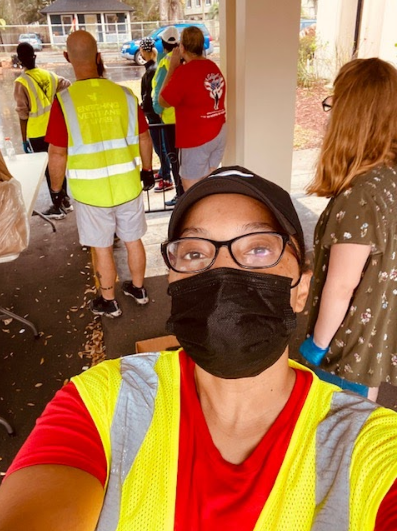 A Stack Up volunteer takes a selfie while other volunteers stand in the background.