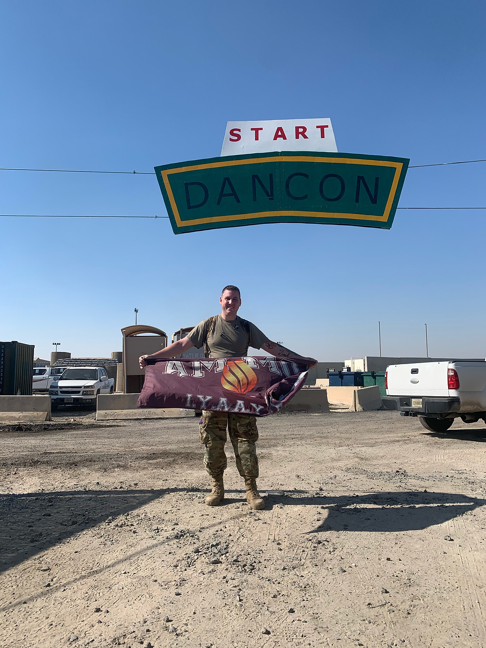 """Derek holds a flag that says """"Ammo"""" under a banner that says """"Start Dancon"""". There are cars around him. He seems to be in a desert parking lot."""