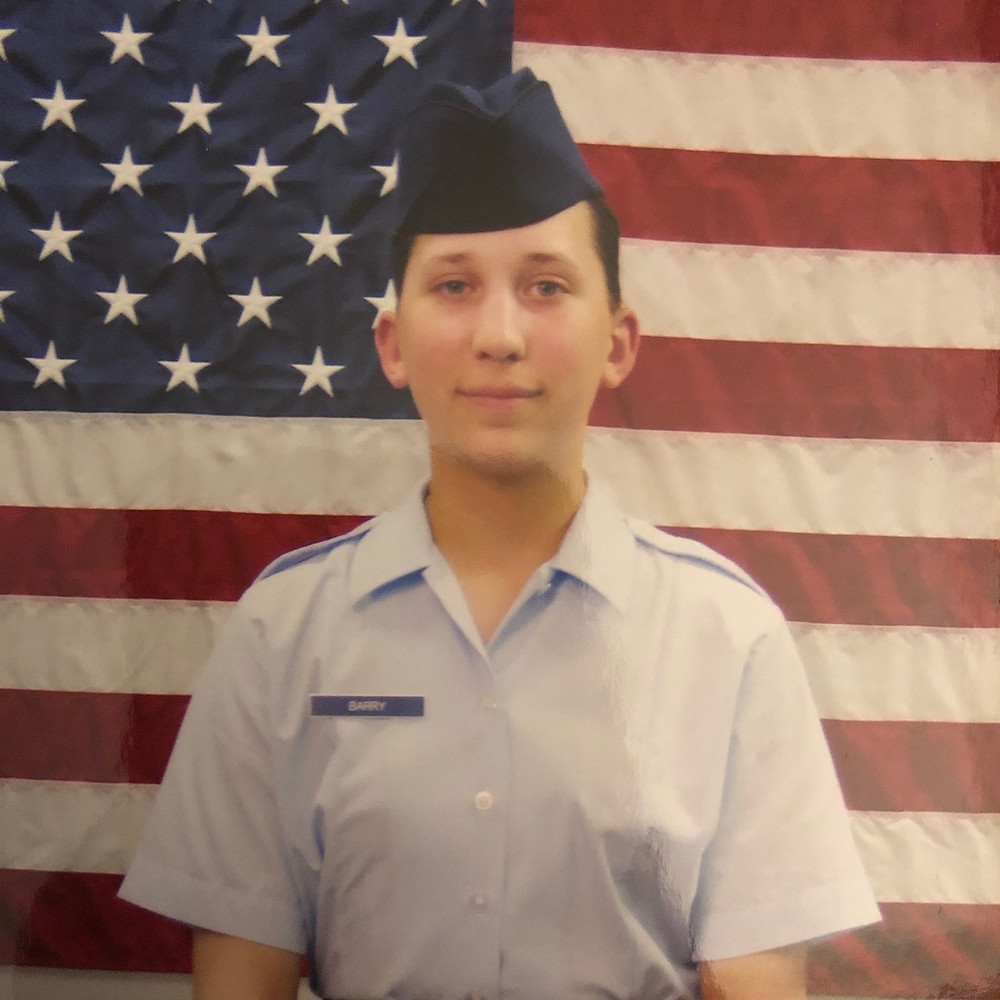 A photograph of Emily in Air Force uniform standing in front of an American flag. She is wearing a blue cap, and light blue button up blouse.