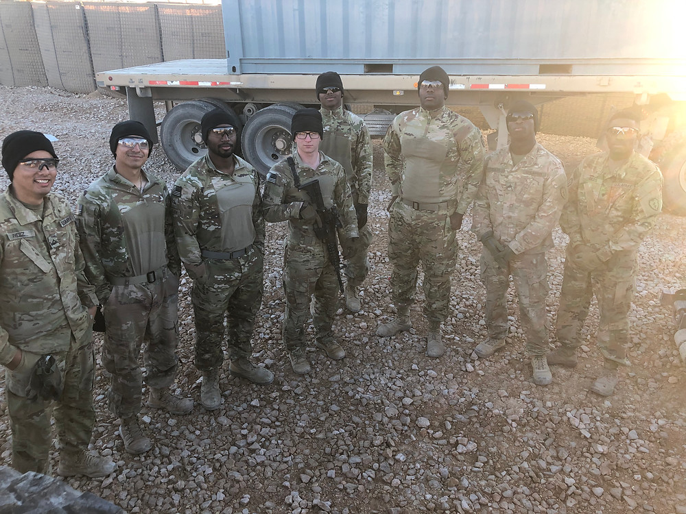8 army soldiers stand in a v shape, smiling and posing for the camera. One of the soldiers in the middle is carrying a rifle. All 8 of them are wearing army camo and black beany caps and bulletproof vests and sunglasses.