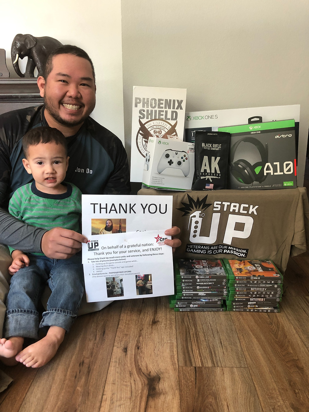 Jonathan with his kid holds up the Stack Up Thank You message from the Supply Crate. The Supply Crate consists of such wonderful gaming goodies as The Division 2 Phoenix Shield Collector's Edition, White Xbox gaming controller, Astro A10 gaming headphones, an Xbox One S, Stack Up T-shirt, and two stacks of xbox videogames. The videogames total 20.