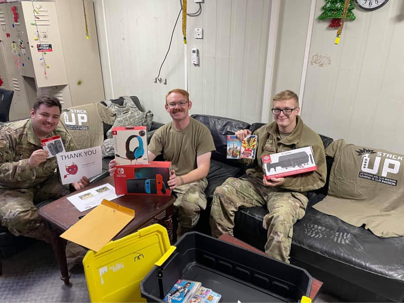 3 Army soldiers sit on a couch with the Stack Up Supply Crate open next to them. They have a new Nintendo Switch, several games, a headset, and extra Nintendo Switch controller. One of the soldiers hold up a Thank You note for Aungelecette.
