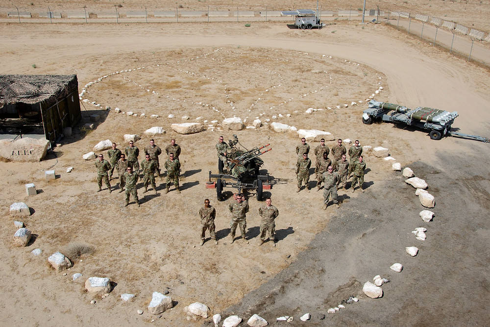 Derek's unit stands in formation in Army uniform inside of a circle made of white rocks. They are in the desert.
