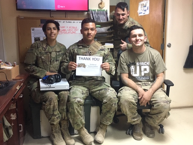 4 soldiers sit in a recreational area. They hold an xbox one s and a thank you note for the Marvel Factor Coalition.