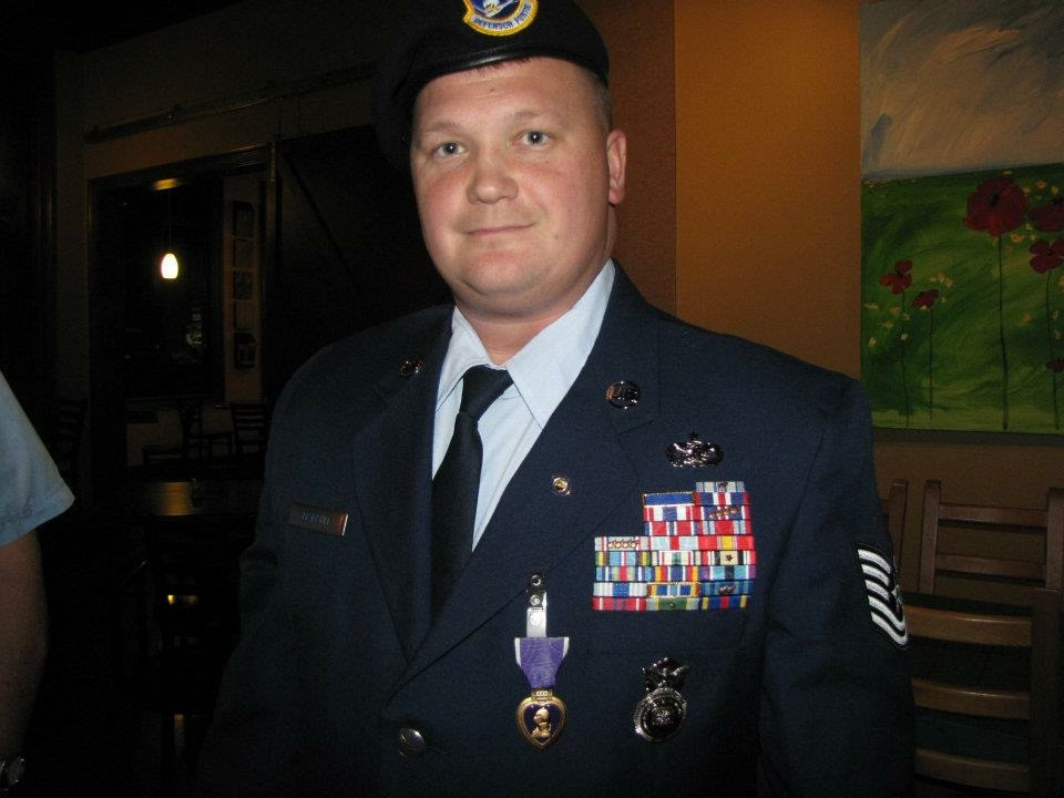 Dustin poses for a photo in full dress uniform. The left side of his chest is covered in award medals and ribbons.