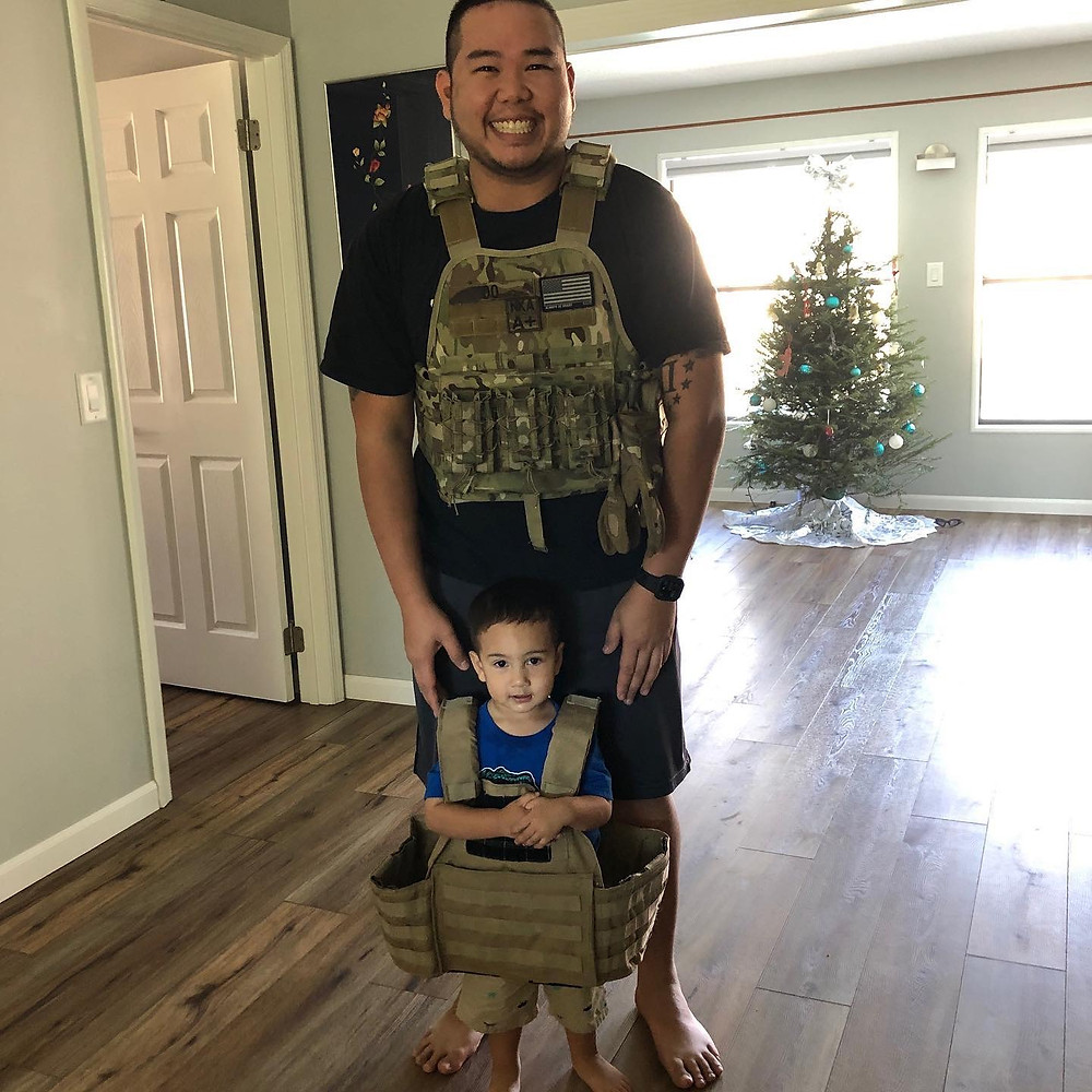 Jonathan stands behind his very small child with his hands on his shoulders. They are both wearing utility vests. The child's utility vest is much too big for him and hangs off his frame. Jonathan is smiling.