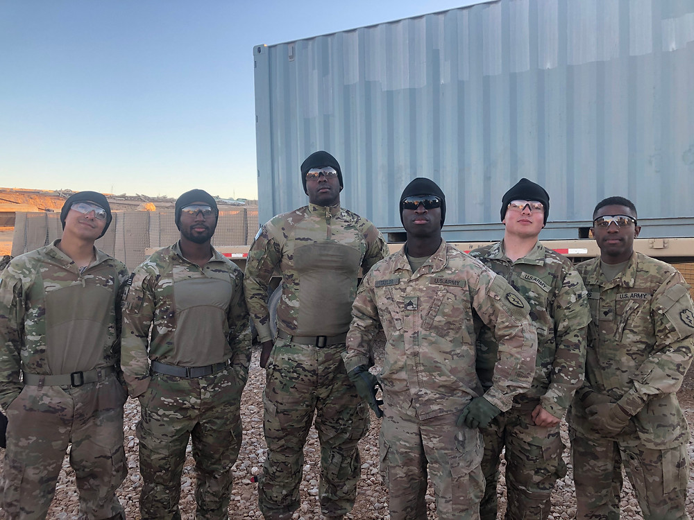 6 army soldiers wearing army camo stand together somewhere in the desert. They are all wearing sunglasses and posing in a faux-serious manner. They all wear bulletproof vests.