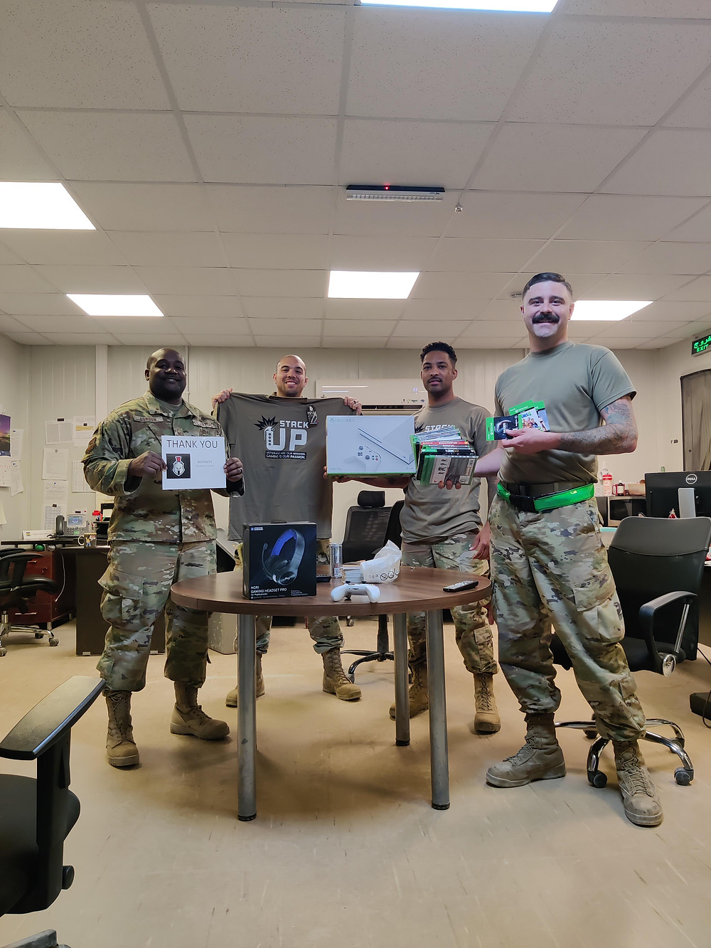 4 soldiers post in a recreation room with an xbox one s console and games.