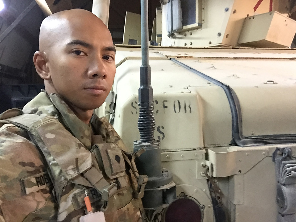 Daryl stands next to a military vehicle. He is in full Army uniform and gear.